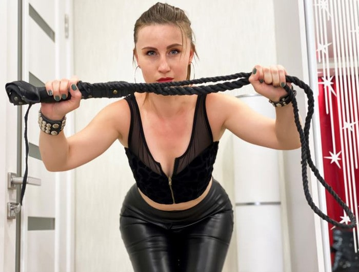 hot pegger dressed in leather holds a whip