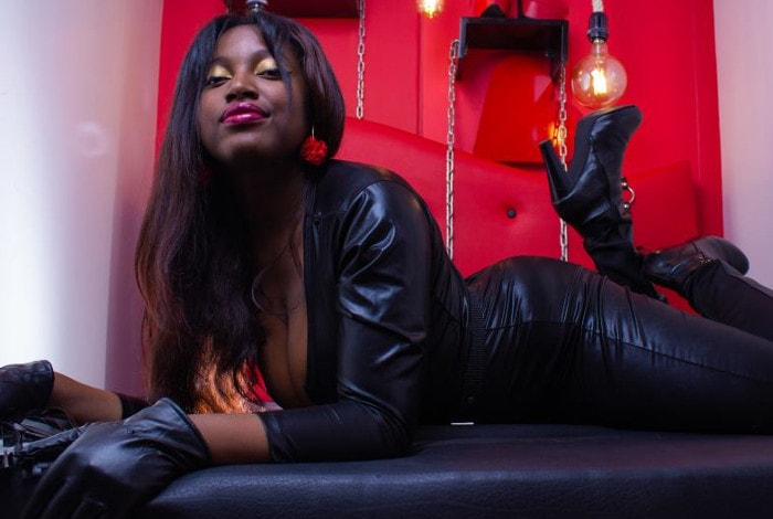 black domme posing in leather and boots