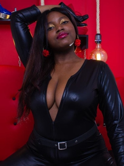 big tits black mistress teases cleavage in leather body suit