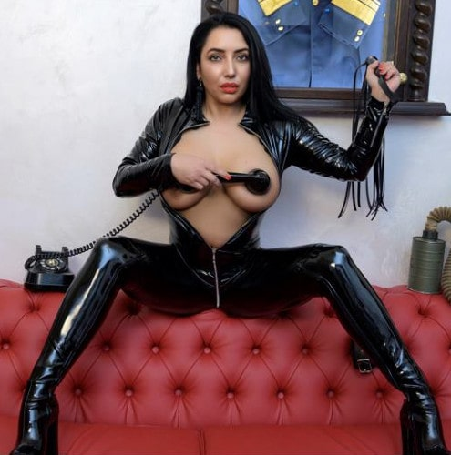 latex draped mistress holding a phone to her tit for some reason