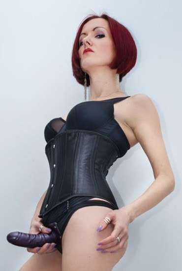 redhead mistress in corset wearing strapon dildo