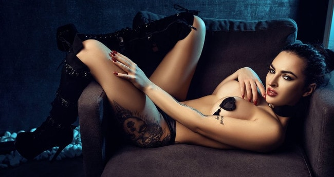 topless brunette domina posing with pastied nipples