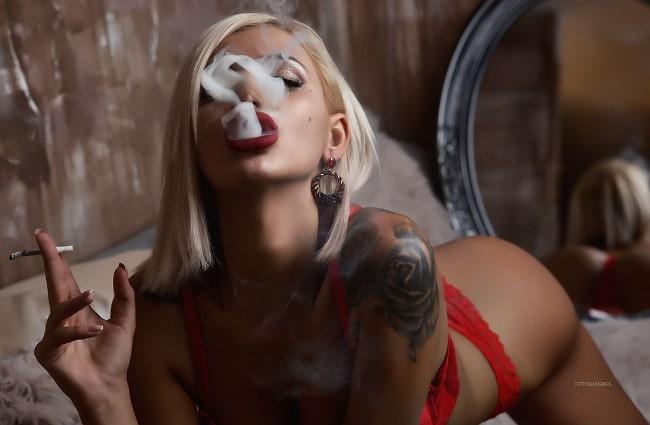 smoking mistress blowing a plume of cigarette smoke